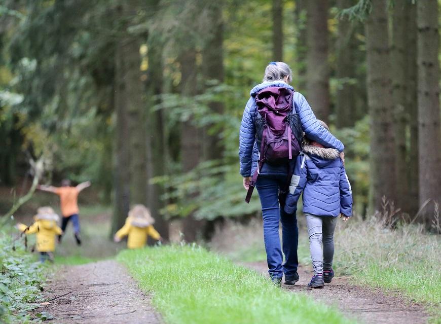 Spendenwanderung: Frau mit Kindern wandern im Wald
